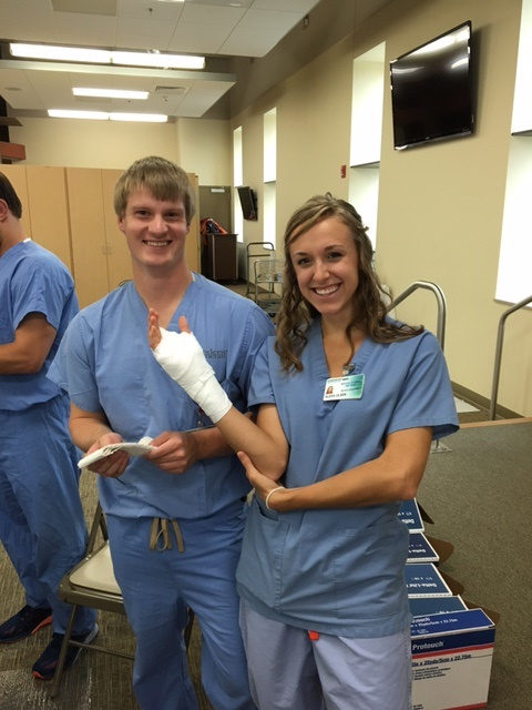 Students put a cast on a wrist
