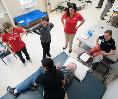 Students gather around a physical therapy table