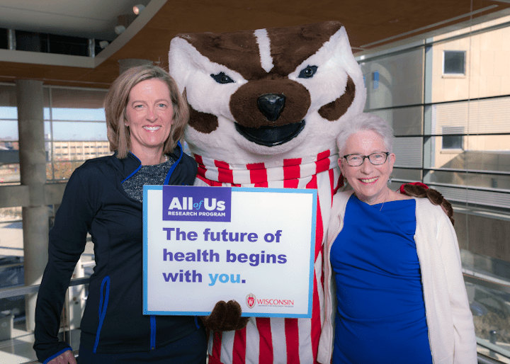 Two women pose with Bucky Badger