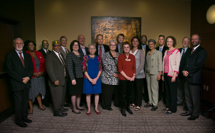 Speakers from a health equity conference pose for a photo with school leaders