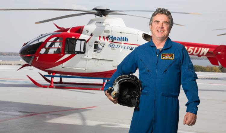 A flight doctor standing in front of a medical helicopter