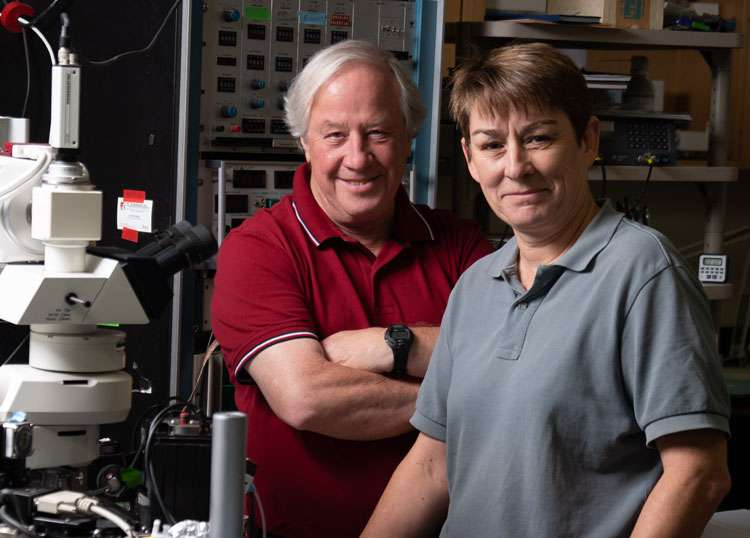 Two researchers posing for a photo in their lab