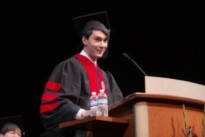 A student in a graduation gown speaking at a podium