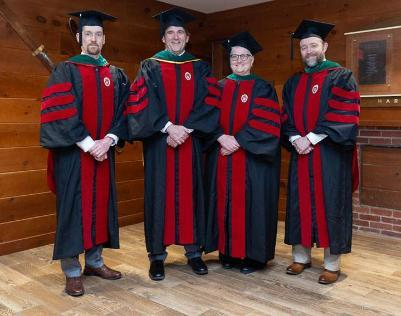 Four faculty members in graduation gowns