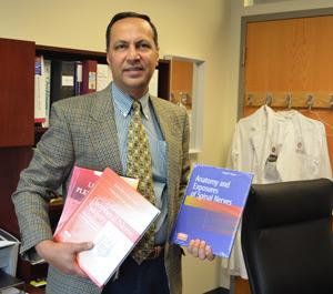 A neurosurgeon holding textbooks