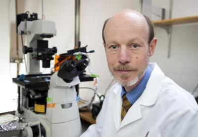 Photo of Tim Kamp sitting next to a microscope