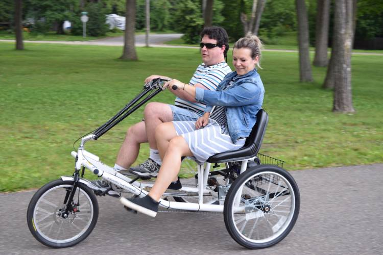 Two people pedaling a three-wheel, two-passenger trike