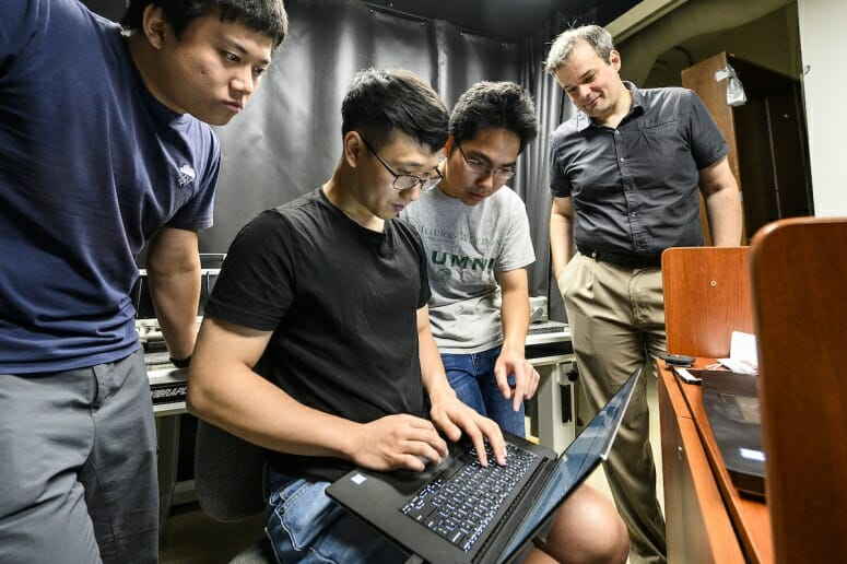 Three students and a professor huddled around a laptop computer