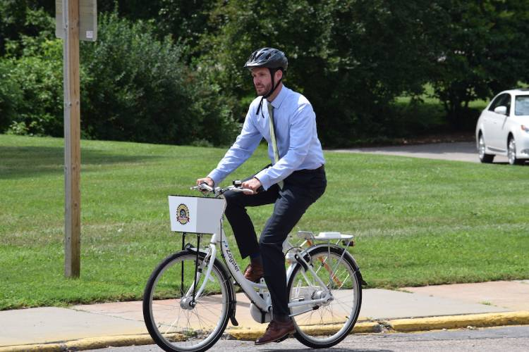A man riding a bike dressed in business attire