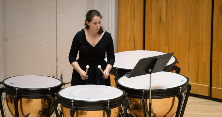 A musician plays a timpani drum