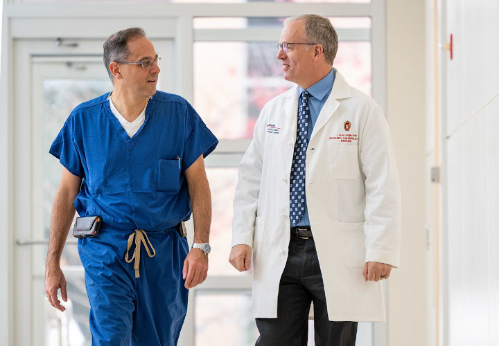 Petros Anagnostopoulos, MD, MBA and J. Carter Ralphe, MD, exchange ideas as they walk through the Health Sciences Learning Center.