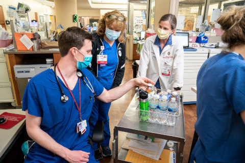 A physician provides water to colleagues