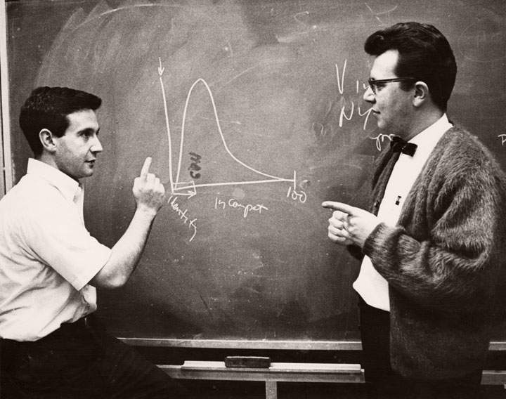 Two academics working at a chalkboard