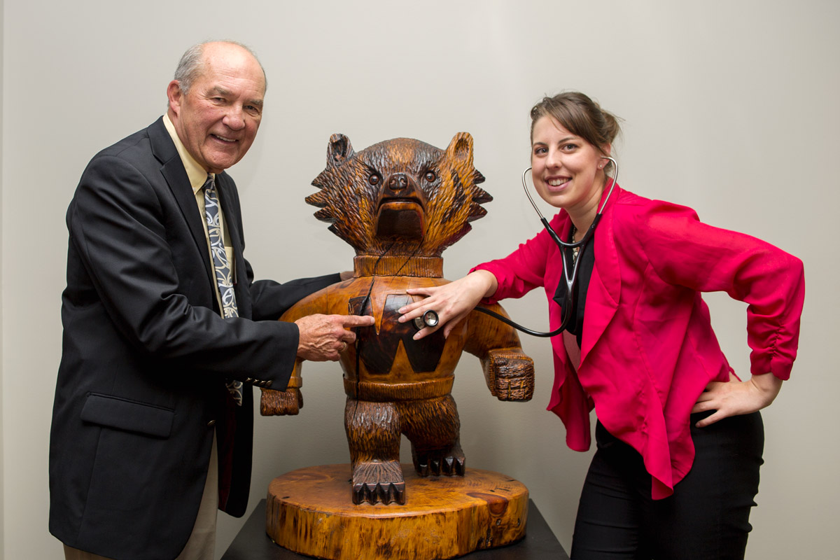 Philip Farrell, MD, PhD and Katie Mooney, MPH posing with a carving of Bucky Badger