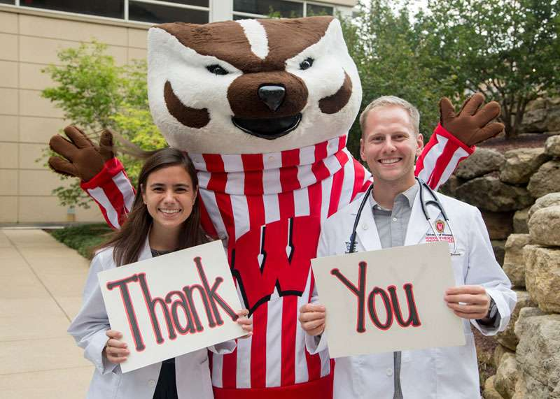 Medical students Katy Jensen and Chris Glover holding signs that say 'thank you'