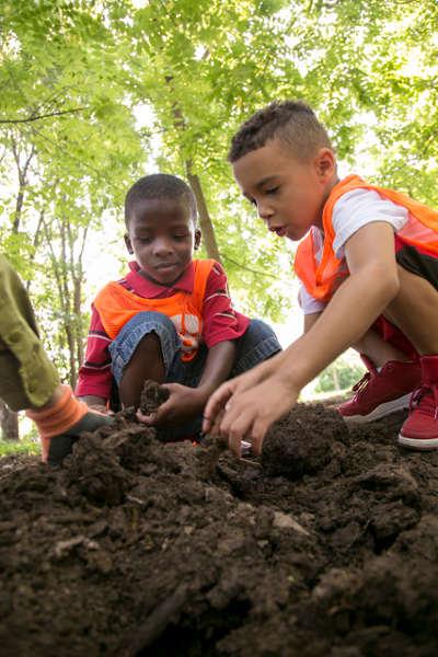 Kids dig through dirt while gardening
